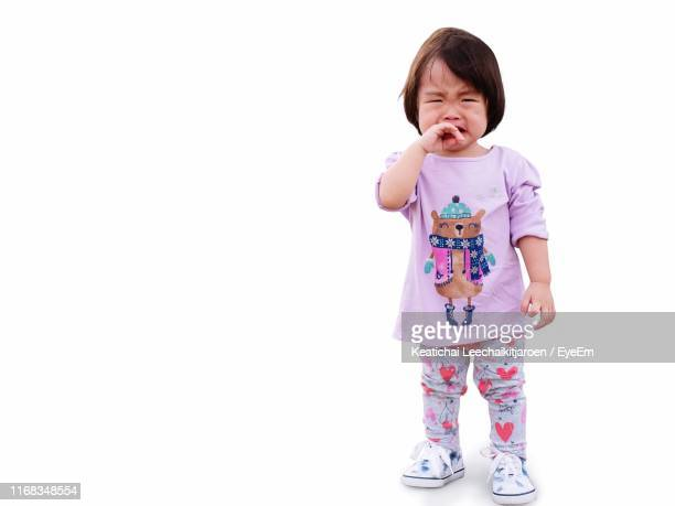 girl crying while standing against white background - sadgirl stock pictures, royalty-free photos & images