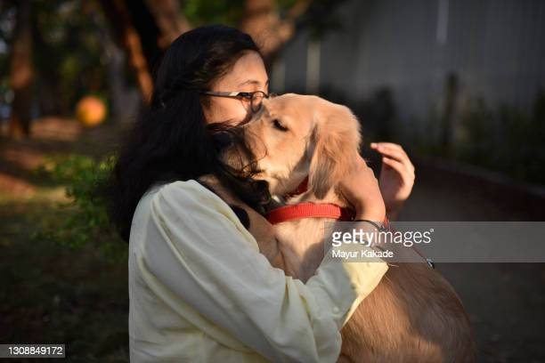 girl cuddling and holding her pet dog - adoption stock pictures, royalty-free photos & images