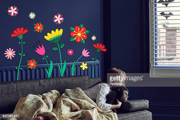 Girl cuddling toy with imaginary flowers
