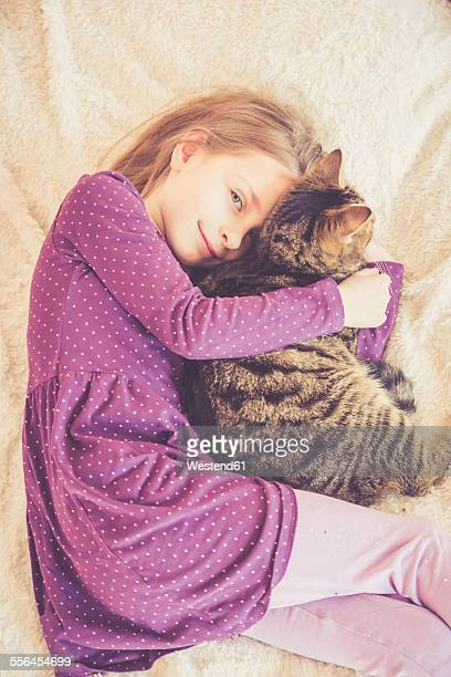 Girl cuddling with cat