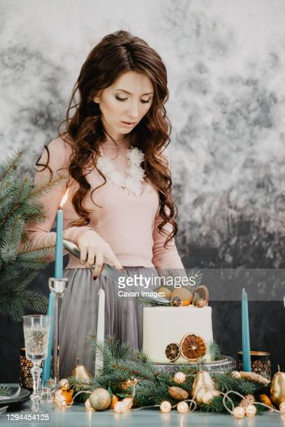 girl cuts christmas cake on a set table on new years eve - 25 29 years stock pictures, royalty-free photos & images