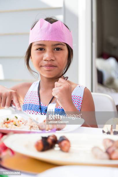 Girl cuts food at Christmas lunch table whilst looking at camera