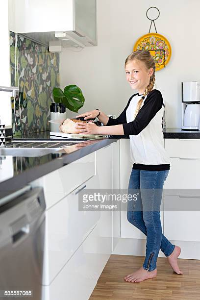 Girl cutting bread in kitchen
