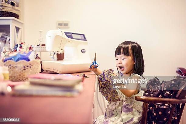Girl cutting cloth with scissors