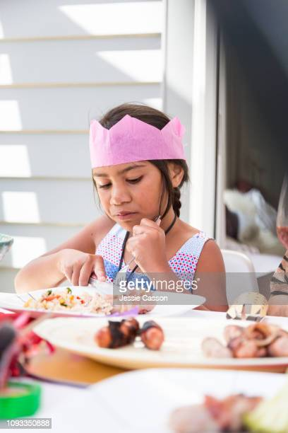 Girl cutting food at outdoor Christmas lunch table