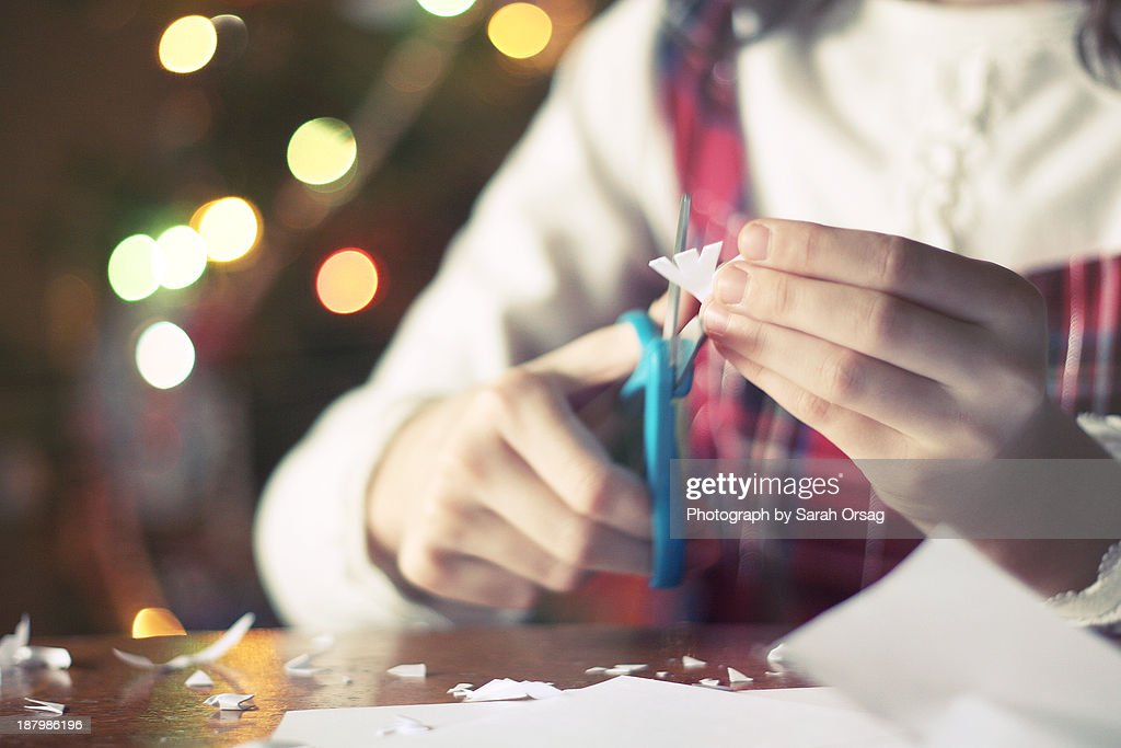 Girl cutting paper snowflakes : Stock-Foto