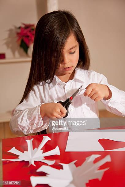 Girl cutting snowflake shape for christmas decoration