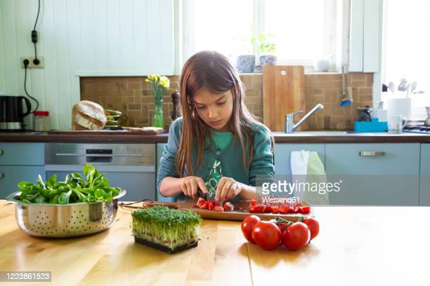 girl cutting tomatoes on chopping board in kitchen - children only stock pictures, royalty-free photos & images