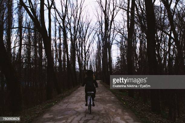 girl cycling on footpath through forest - nikitina stock pictures, royalty-free photos & images