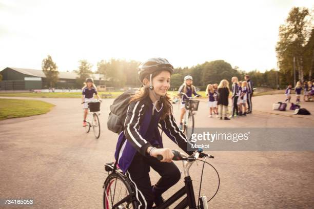 Girl cycling on footpath with friends against sky