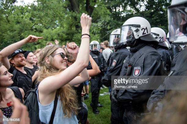A girl dance to techno music in front of the police while they attend a protesters march under the topic 'Grenzenlose Solidaritaet statt G20' against...