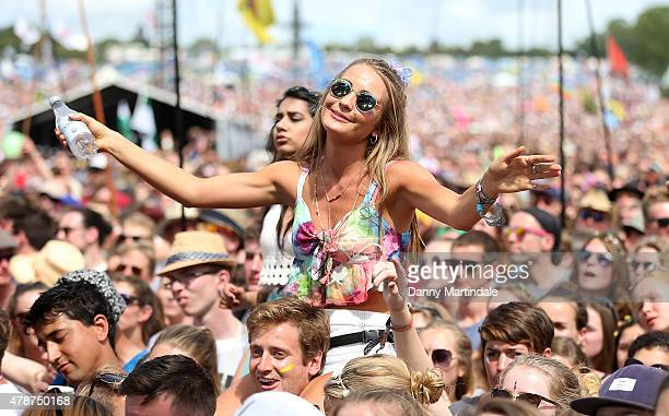 A girl dances on the sholders of a friend as the watch George Ezra at the Glastonbury Festival at Worthy Farm Pilton on June 27 2015 in Glastonbury...