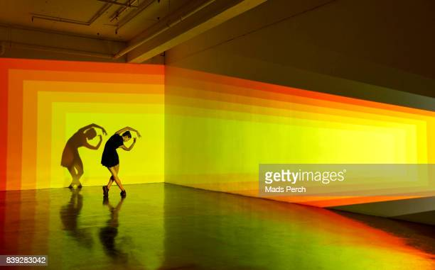 girl dancing in a large space with graphic patterns projected around her - performance stock pictures, royalty-free photos & images