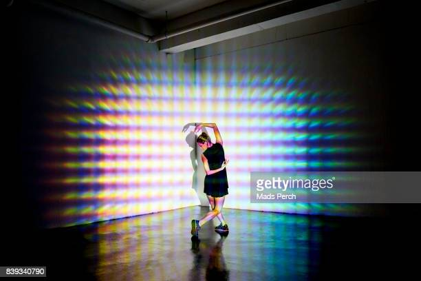 girl dancing in a studio with graphic patterns projected onto her - projektion stock-fotos und bilder