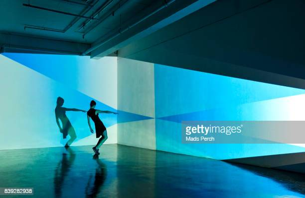 Girl dancing in an abstract space with a projected pattern behind her