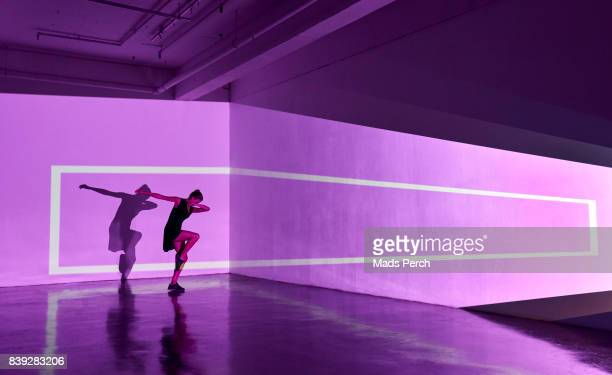 girl dancing in an abstract space with graphics shapes projected behind her - performing arts event stock pictures, royalty-free photos & images