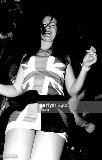 Girl dancing in club wearing union jack dress smilling Brighton 1990s