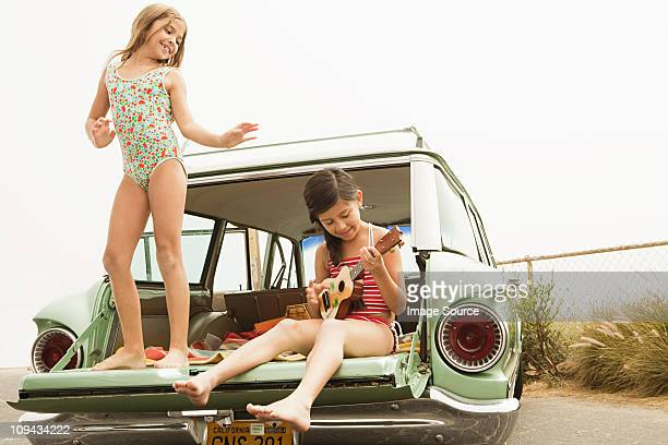 Girl dancing on car boot, another girl playing guitar