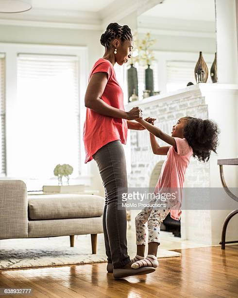 girl dancing on mothers feet