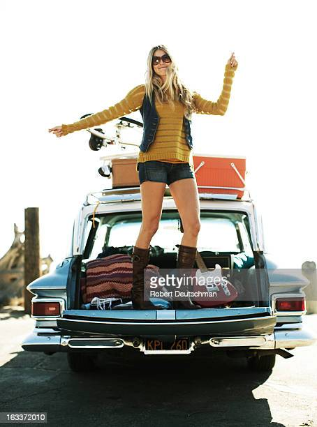 A girl dancing on the tailgate of a classic car.