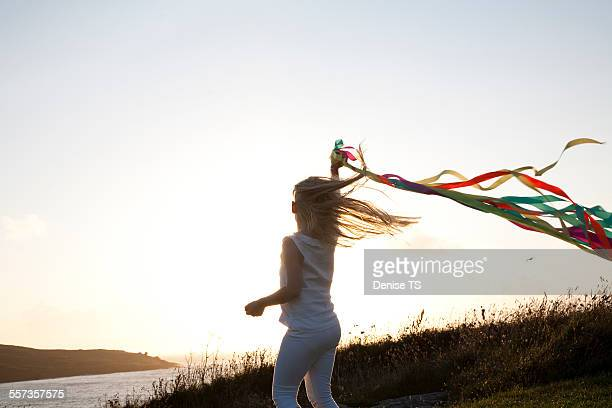 Girl dancing with ribbons near the beach