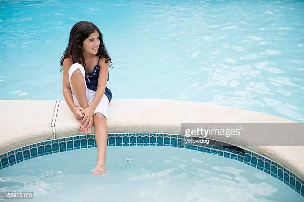 Girl dangling foot in swimming pool