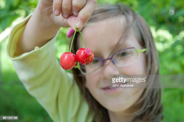 girl dangling pair of cherries - morhange photos et images de collection
