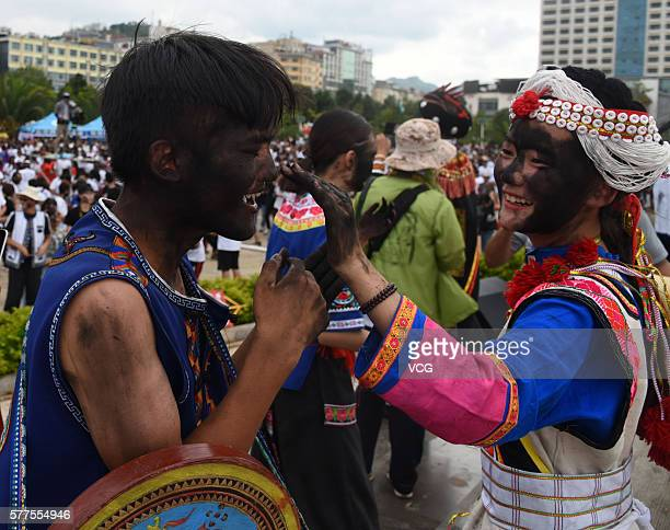Girl daubs rice ash on a boy's face during the Face Painting Festival in Puzhehei Resort of Qiubei County on July 18, 2016 in Wenshan Prefecture,...