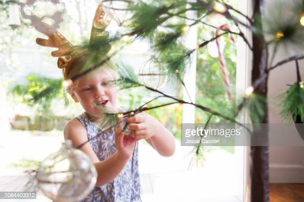 A girl decorates a Christmas tree with homemade decorations