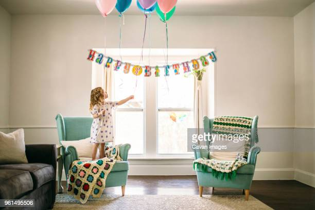 girl decorating balloons in living room for birthday party - party decoration stock pictures, royalty-free photos & images