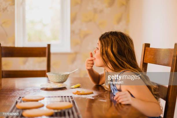 Girl decorating biscuits at home