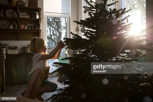 Girl decorating Christmas tree in backlight