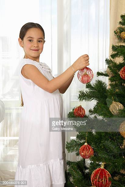 Girl (7-9) decorating Christmas tree, portrait