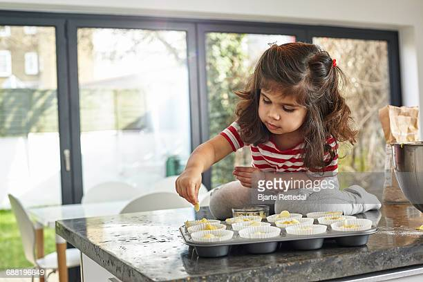 girl decorating cupcakes in domestic kitchen - bjarte rettedal stock pictures, royalty-free photos & images