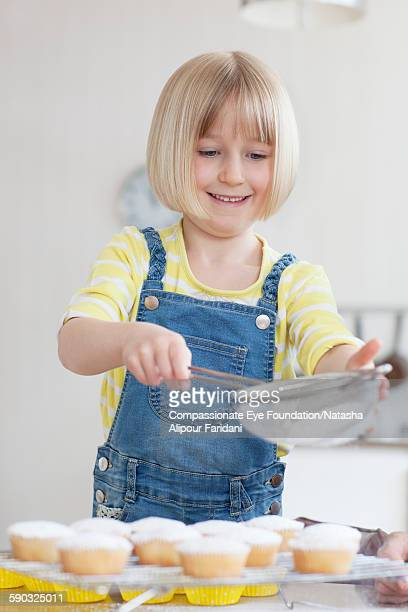 Girl decorating cupcakes in kitchen