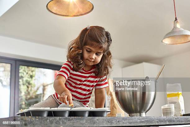 girl decorating cupcakes - bjarte rettedal stock pictures, royalty-free photos & images
