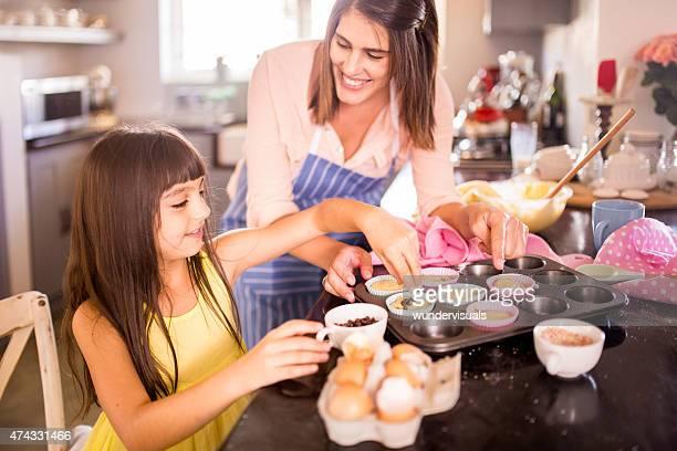 Mädchen Dekoration cupcakes Sie hilft, ihre Mutter machen
