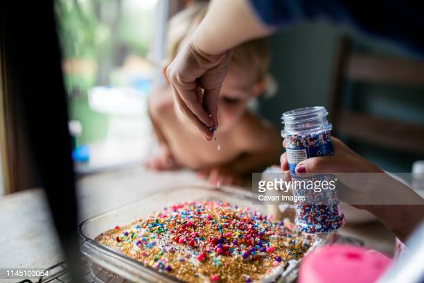 girl decorating freshly baked cake with plenty of sprinkles - decorating a cake stock pictures, royalty-free photos & images