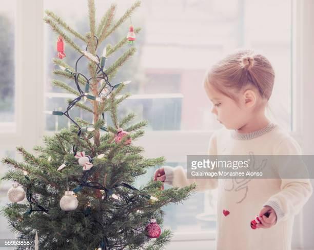 Girl decorating small Christmas tree
