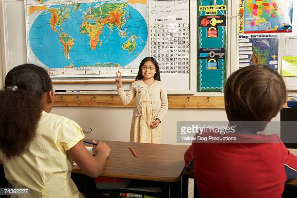 Girl (8-9) demonstrating peace sign in front of classroom, other students watching