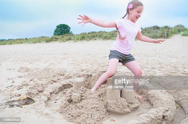 menina destruir castelo de areia na praia - destruição imagens e fotografias de stock