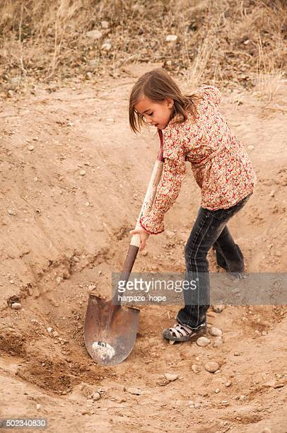 Girl Digging a Hole with a Shovel