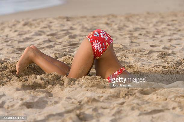 girl (5-7) digging hole in sand on beach, side view, low section - chinese bikini girls stock pictures, royalty-free photos & images