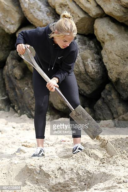 A girl digs with a spade as she searches a beach in Folkestone southeast England on August 29 2014 for gold bullion buried there by German artist...