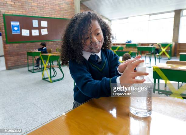 girl disinfecting her hands at school using hand sanitizer - biosecurity stock pictures, royalty-free photos & images