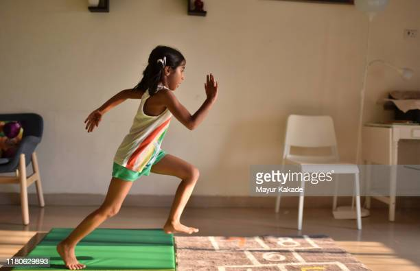 girl displaying her athletics skills at home - hurdling track event stock pictures, royalty-free photos & images