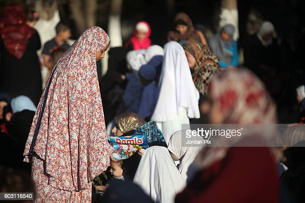 A girl distributes candy to women as thousands of Jordanian worshippers attend a central Eid Al Adha prayer at King Hussein sports city on September...