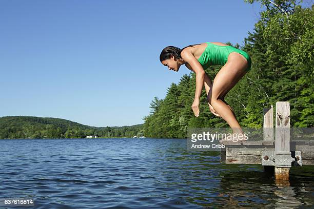 Girl dives into a calm summer lake in Vermont countryside