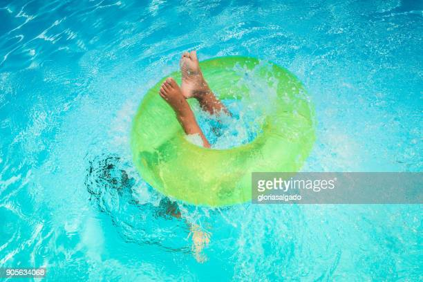 Girl diving through an inflatable rubber ring in a swimming pool
