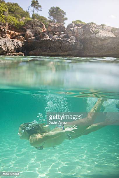 girl diving underwater in the mediterranean sea - islas baleares fotografías e imágenes de stock
